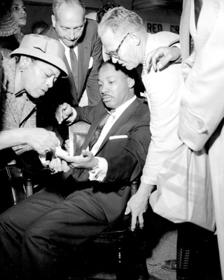 Martin Luther King, Jr., with letter opener protruding<br/> from his chest, after he was stabbed at a bookstore<br/> in Harlem.